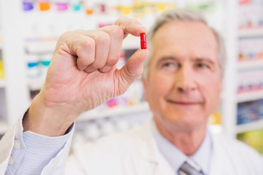 Smiling pharmacist in lab coat showing pill