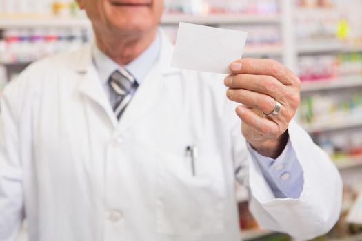 Senior pharmacist reading calling card