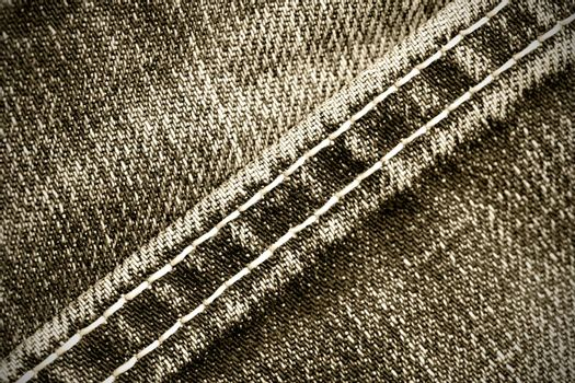 part of old jeans background with diagonal seams. monochrome image