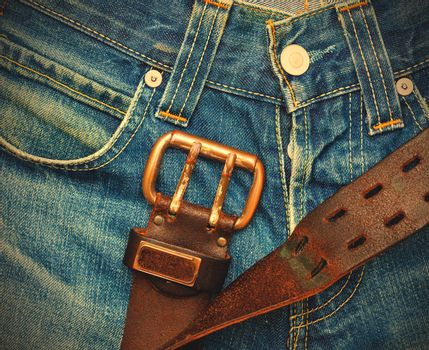 Vintage leather belt with metal buckle on old blue jeans. instagram image retro style
