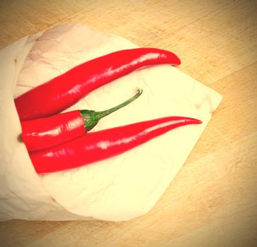 red hot chili peppers in paper bags on a wooden background. instagram image style