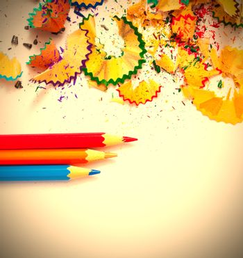 colored pencils and shavings on white background with copy space. instagram image retro style