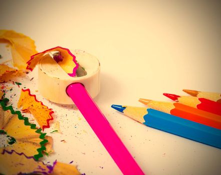 set of colored pencils, sharpener and shavings on white background with copy space. instagram image retro style