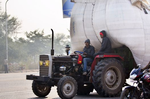 Jaipur, India - December 30, 2014: Indian man driving Heavily overloaded truck in Jaipur, Rajasthan, India.
