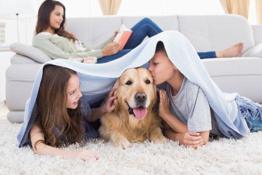 Siblings with dog under blanket