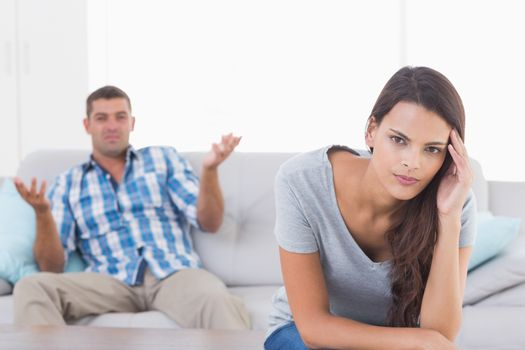 Woman suffering from headache while man quarreling