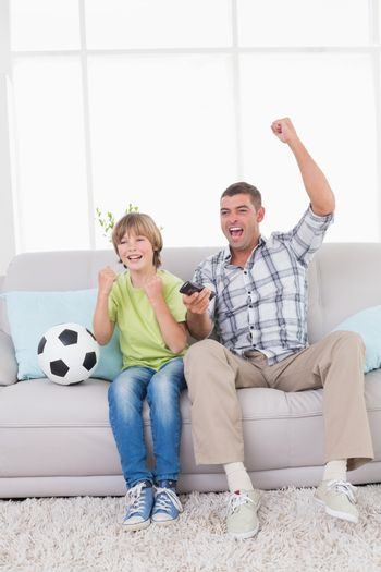 Happy father and son celebrating success while watching soccer match at home