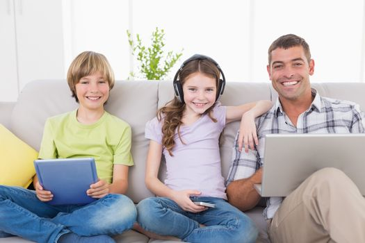 Portrait of happy man with children using technologies while sitting on sofa at home
