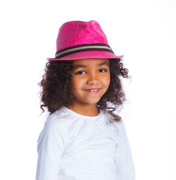 Closeup portrait of a pretty mulatto girl in pink hat smiling at camera on white background