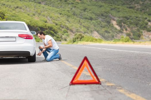 Man changing wheel after a car breakdown