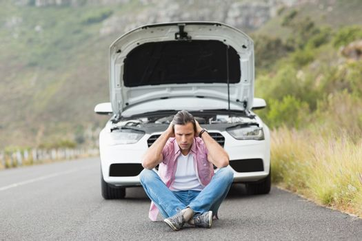 Stressed man sitting after a car breakdown
