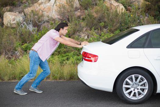 Man pushing car after a car breakdown