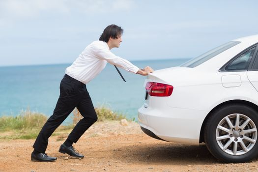Businessman pushing his car