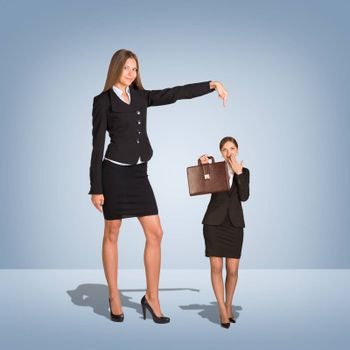 Smiling Young Businesswoman Pointing to small Businesswoman with briefcase. Blue background