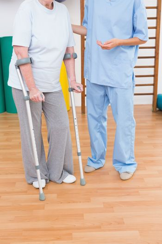 Therapist helping senior woman with scrubs