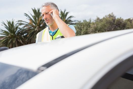 Unsmiling man calling for assistance after breaking down