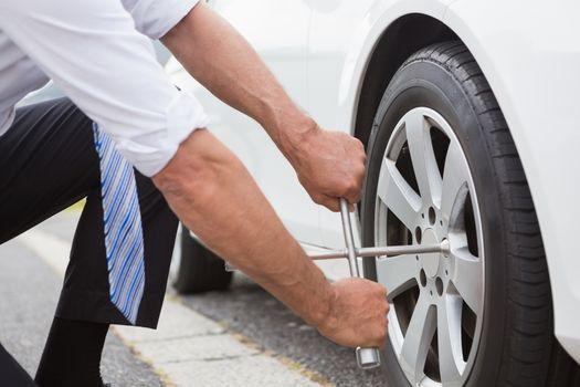 Businessman fixing tire