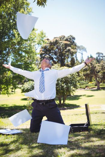 Businessman tossing papers in the park