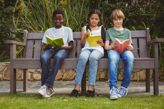 Portrait of children reading books at the park