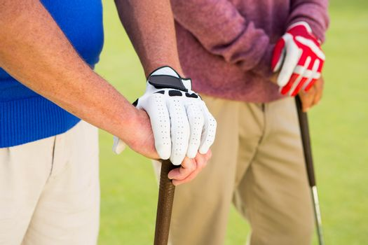 Golfing friends standing and holding clubs at golf course
