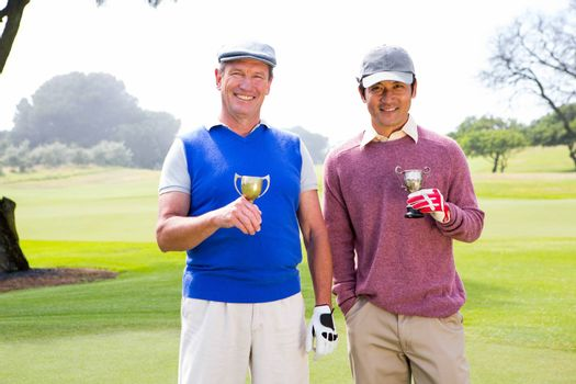 Golfing friends holding cups smiling at camera at golf course