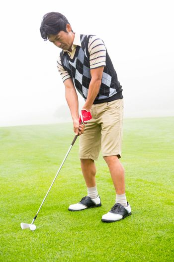Concentrating golfer lining up his shot