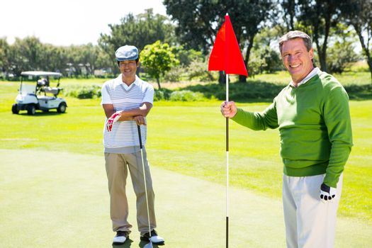 Golfing friends smiling at camera at the golf course