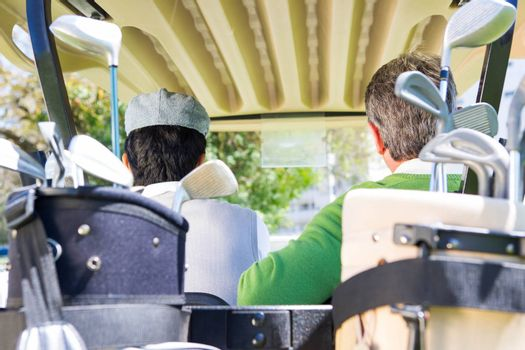 Golfing friends driving in their golf at the golf course