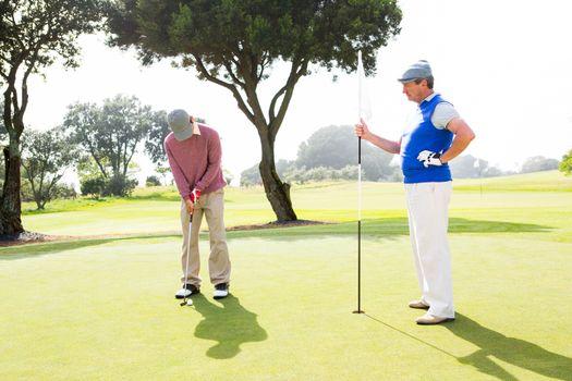 Golfer swinging his club with friend