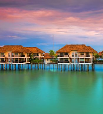 Water villas making reflections in the ocean at sunset