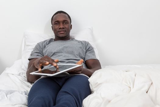 Man looking at camera and touching his tablet