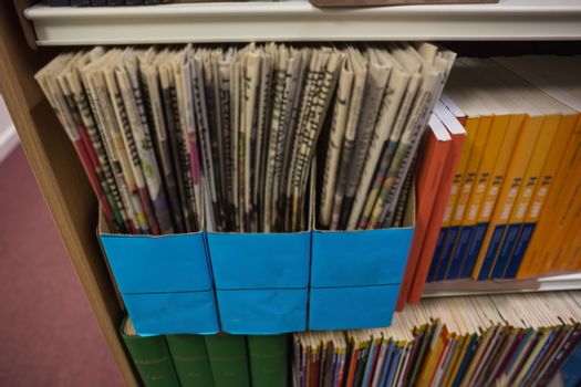 Newspapers on bookshelf in library