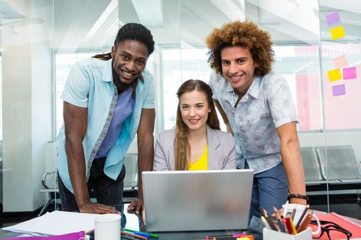 Creative young business people using laptop at office desk