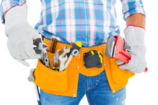 Midsection of handyman holding hand tools
