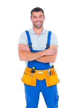Repairman in overalls wearing tool belt standing arms crossed