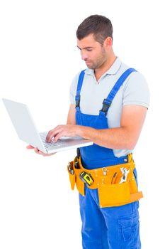 Carpenter in blue overalls using laptop