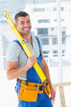 Happy repairman in overalls holding spirit level in office