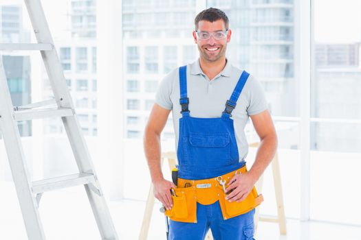 Smiling repairman in overalls at bright office