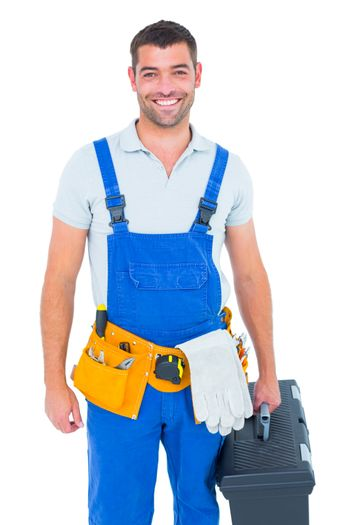 Happy workman in overalls holding toolbox
