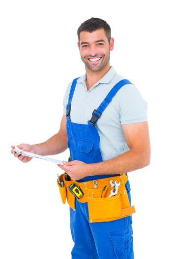 Happy carpenter in overalls holding clipboard