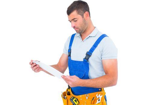 Male carpenter in overalls reading clipboard