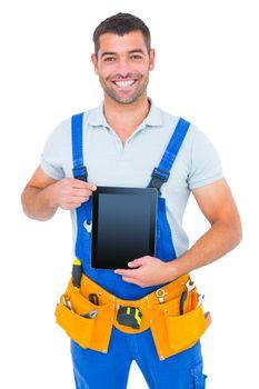 Happy repairman in overalls holding digital tablet