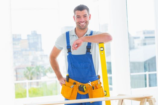 Carpenter in overalls with spirit level in office