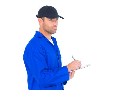 Mechanic in blue overalls writing on clipboard