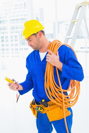 Electrician reading multimeter in bright office