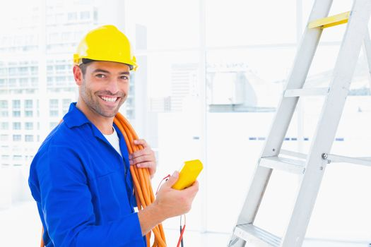 Smiling male electrician holding multimeter in office