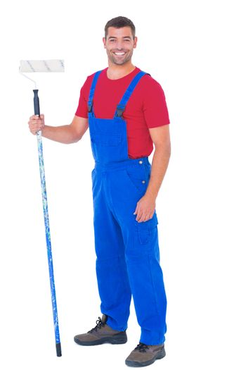 Handyman in overalls holding paint roller on white background