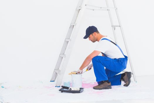 Side view of handyman in overalls opening paint can