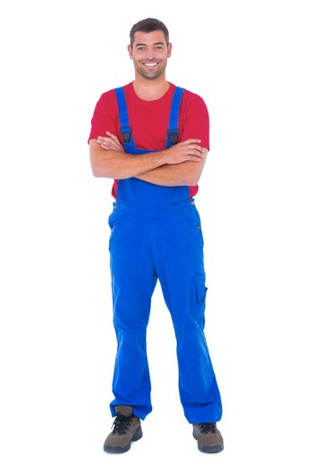 Handyman in overalls standing arms crossed over white backgound