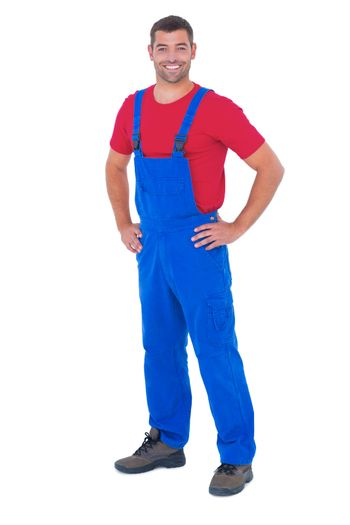 Happy handyman in overalls with hands on hip